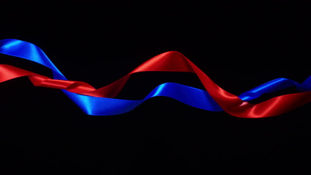 red and blue ribbons on black background, for celebration events and party for new year, birthday party, christmas or any holidays, waiving and curling in super slow motion and close up - loopable moving image stock videos & royalty-free footage