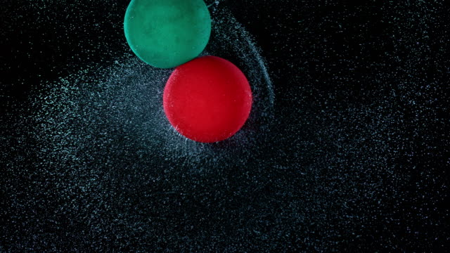 slo mo ld red and green balloon rotating in the air and spraying water while colliding - two objects stock videos & royalty-free footage