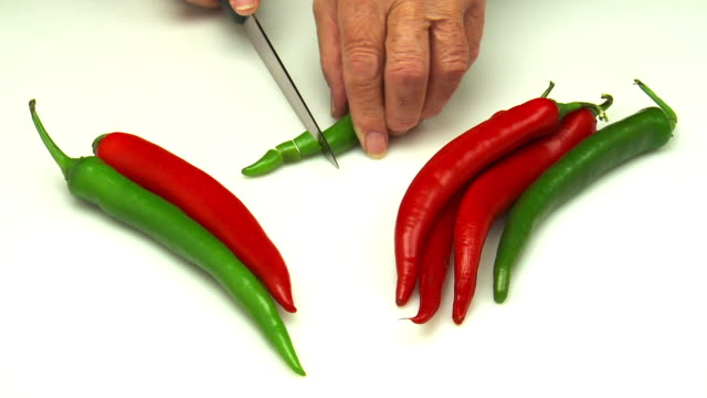 red and green chile peppers sliced on white ground