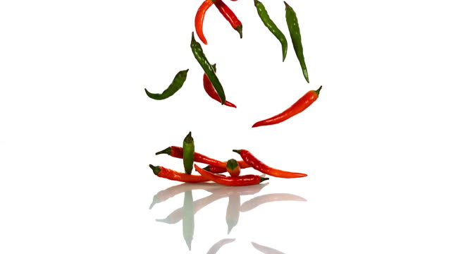 red and green chili peppers, capsicum annuum falling against with background, slow motion - peperoncino video stock e b–roll