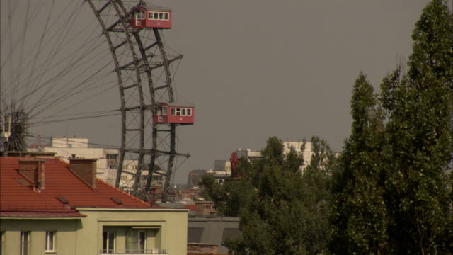 red and green roofs cover buildings below the riesenrad ferris wheel in prater amusement park in vienna, austria. available in hd - prater park stock videos & royalty-free footage