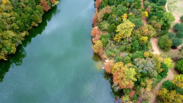 vídeos de stock e filmes b-roll de red and orange tree line the coastline of the colorado river in austin , texas - town