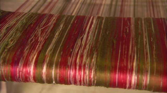 red and pink threads cover a loom. - textile mill stock videos & royalty-free footage