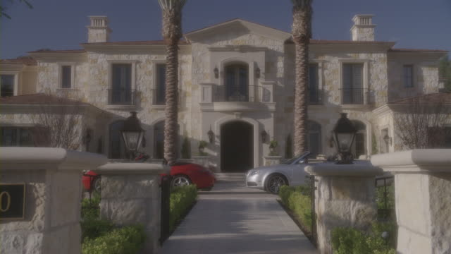 stockvideo's en b-roll-footage met red and silver convertibles park outside a beverly hills mansion. - landhuis
