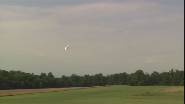 a red and white biplane flies close to a field with stuntwoman jane wicker waving from the wings. - stunt person stock videos & royalty-free footage