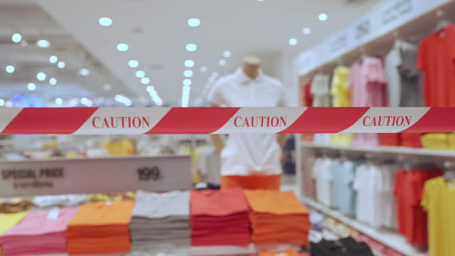 vídeos de stock, filmes e b-roll de sinal de fita de cautela vermelho e branco em situação de vírus covid-19 em frente a loja de roupas - placa