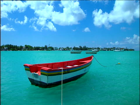 Red and white colourful small rowing boat moored in turquoise sea with white fluffy clouds above.