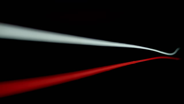 slo mo ld a red and white fibre moving against black background - two objects stock videos & royalty-free footage