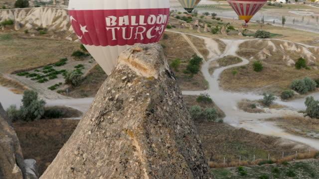 A Red and White Hot Air Balloon Gets Close to a Basalt Spire - Cappadocia, Turkey