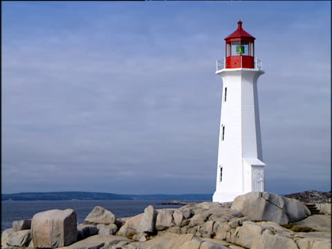 red and white lighthouse and rocks yellow house with canada flag on barren land - canadian flag stock videos & royalty-free footage