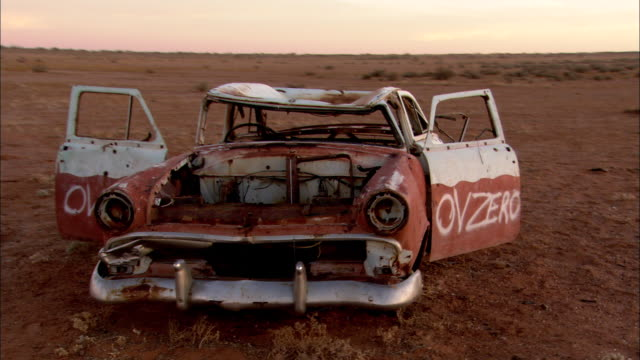 ms tu ds red and white rusted car  with doors open in desert at sunset, anna creek, south australia, australia - 荒廃した点の映像素材/bロール