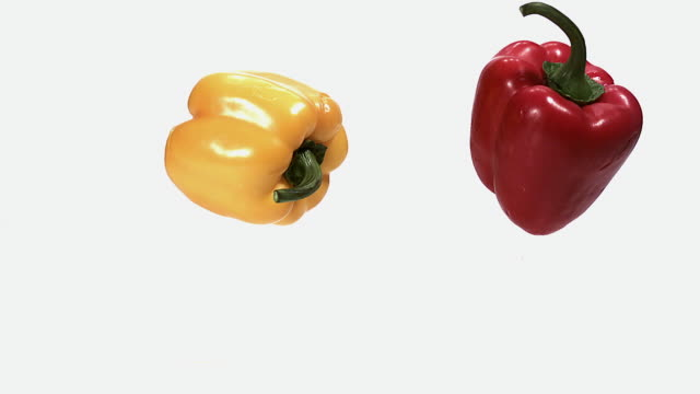 ms slo mo red and yellow capsicum falling on floor against white background / vieux pont, normandy, france  - パプリカ点の映像素材/bロール