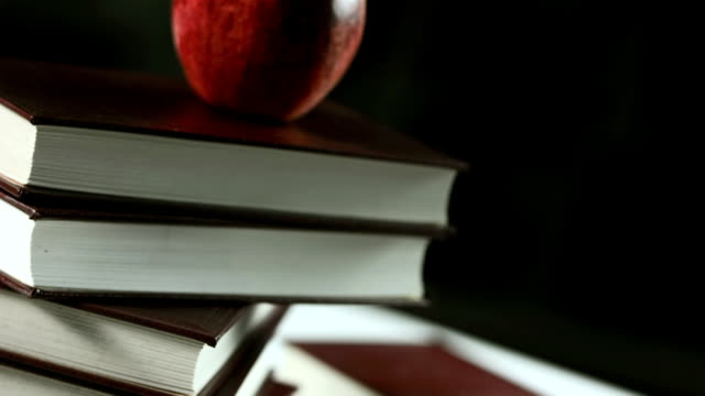 hd: red apple on books - textbook stock videos and b-roll footage