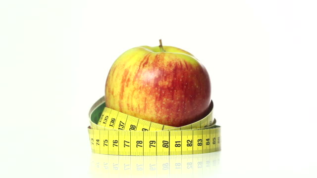 red apple with tape measure - frische stock videos & royalty-free footage