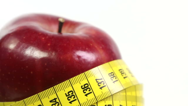 red apple with tape measure - drehen stock videos & royalty-free footage