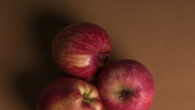 Red apples over brown background