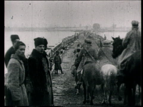 1920 montage b/w ws red army cavalry crossing bridge on horseback, watched by military commander, kliment voroshilov/ ws cavalry soldiers riding past on horseback - cavalry stock videos & royalty-free footage