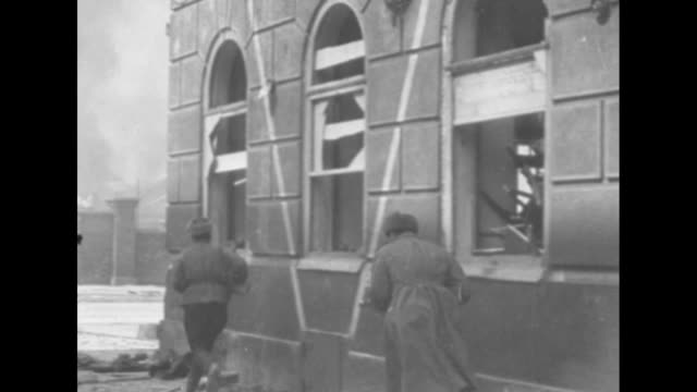 [Red Army footage of Vienna Offensive of World War II] Red Army soldiers crouch as they run around and into building / rear shot sniper fires out...