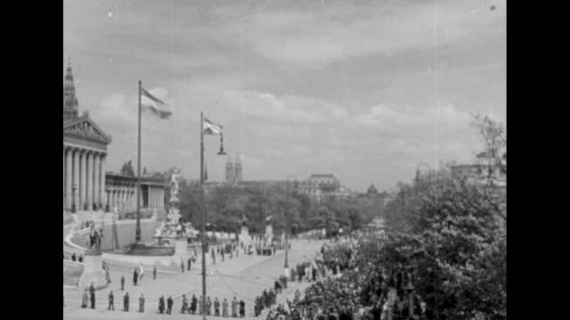 [Red Army footage of Vienna Offensive of World War II VO music throughout] Austrian flag flutters atop Vienna's City Hall / smiling Austrian civilian...