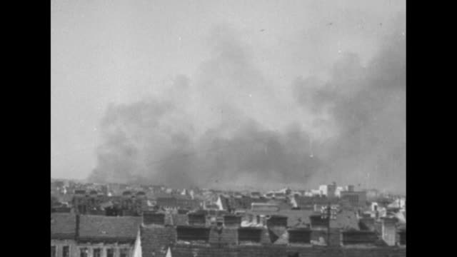 [red army footage of vienna offensive of world war ii, with vo music throughout] military airplane in sky; tilt down to skyline of vienna, with smoke... - world war ii video stock e b–roll