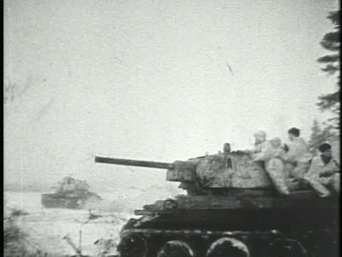 vidéos et rushes de red army soviet russian tanks driving on snow out of forest, soldiers in white oversuits riding tank over tree fg, soldiers in dark coats & hats... - char véhicule blindé