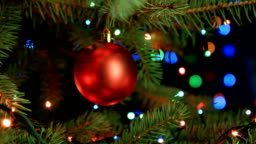 red ball close up hanging on the Christmas tree, Christmas song 2017 on the background of blurred lights garlands