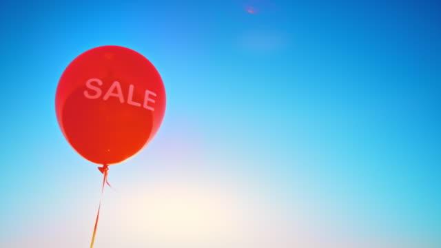 vídeos y material grabado en eventos de stock de slo mo ld globo rojo con inscripción 'venta' flotando en el aire - globo de helio
