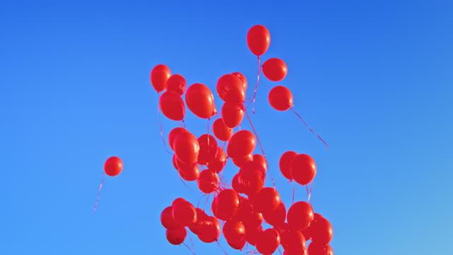 vídeos y material grabado en eventos de stock de slo mo ld globos rojos con inscripción 'venta' flotando en el cielo azul - globo de helio