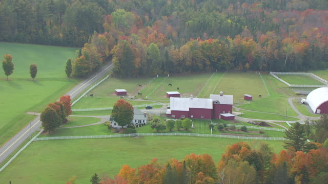 WS AERIAL POV Red barn and farmhouse on landscape in autumn / Barnet, Caledonia County, Vermont, United States