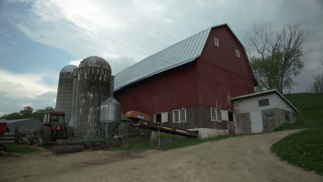 red barn and grain silos on a dairy farm - 乳製品工場点の映像素材/bロール
