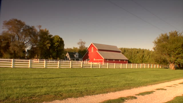 ws red barn w/ white fence in front grassy field w/ dirt path trees power lines upper right gray/blue sky - barn stock videos & royalty-free footage