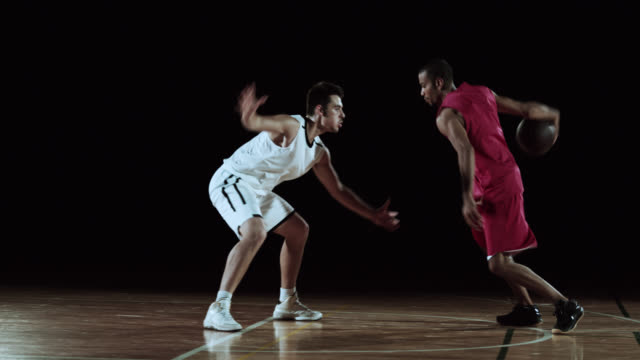 SLO MO of red basketball player dribbling the opponent