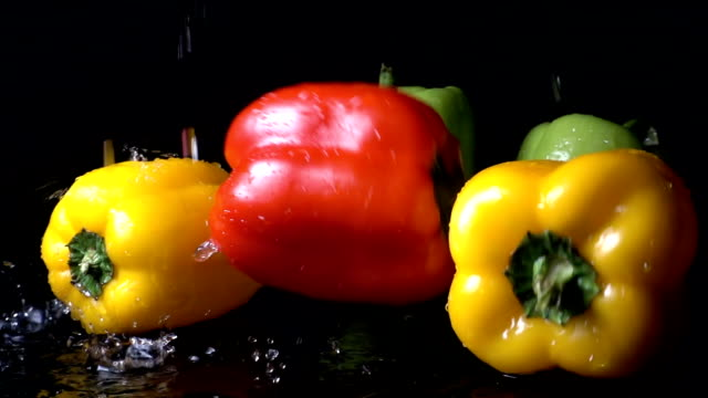 red bell pepper falling against black background - peperone dolce video stock e b–roll