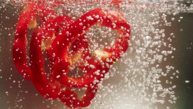 red bell pepper slices falling down into boiling water - pepper pot stock videos & royalty-free footage