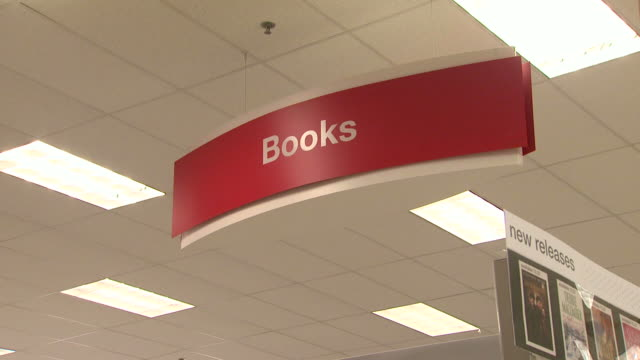 red books sign underneath fluorescent light panels in ceiling new releases sign bookshelves filled with hardcovers in target / united states - hardcover book stock videos and b-roll footage