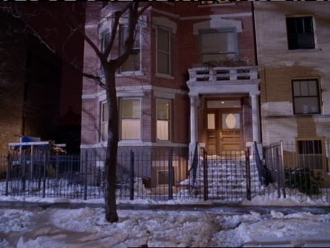 a red brick townhouse stands in a snowy yard. - elevated train stock videos & royalty-free footage
