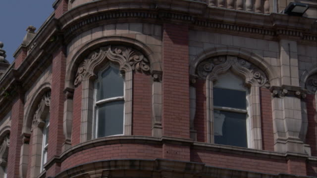A red brick Victorian building features ornate arched windows. Available in HD.