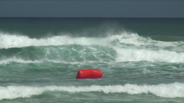 ws red buoy in ocean waves / 90 mile beach, new zealand - new zealand stock-videos und b-roll-filmmaterial