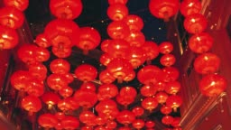 Red burning chinese lanterns rise into the air along a city street