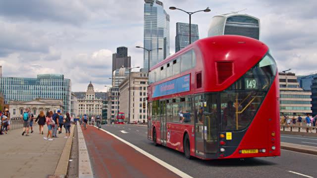 roter bus auf der london bridge. finanzdistrikt im hintergrund - doppeldeckerbus stock-videos und b-roll-filmmaterial