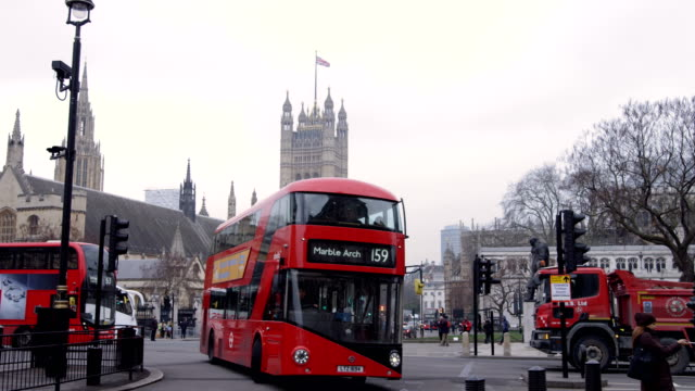 red buses turns right at parliament square in slow motion - autobus a due piani video stock e b–roll