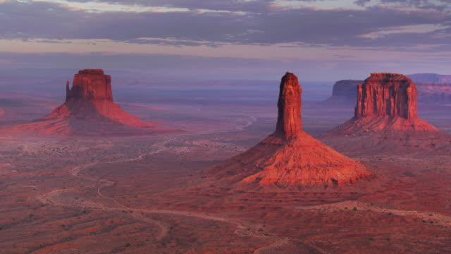 red buttes and mesas in evening light in monument valley - panning drone shot - monument valley stock videos & royalty-free footage