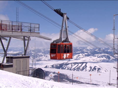 Red cable car arriving at top of snow covered ski slope snow peaked mountain ranges in background