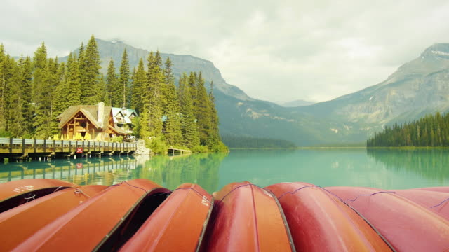 red canoes on emerald lake in canada. - see stock-videos und b-roll-filmmaterial