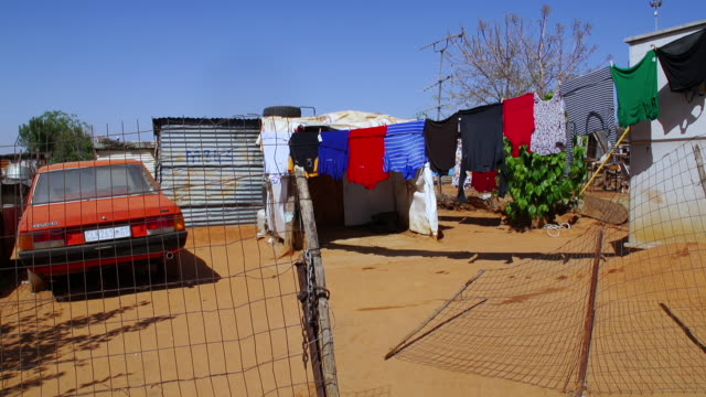WS Red car parked outside of corrugated iron shack, washing on line foregrounded / Cosmo City, South Africa