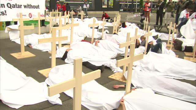 """red card for fifa"" demonstrators setting up mock graves, wooden crosses in protest of worker deaths during qatar world cup preparation as fifa... - fifa stock videos & royalty-free footage"