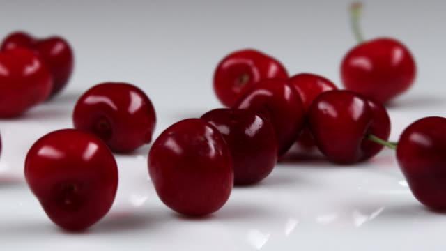 red cherries falling onto table. - オレム点の映像素材/bロール
