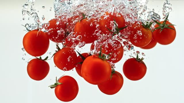 vídeos de stock, filmes e b-roll de slo mo ld tomates de cereja vermelho caindo na água - tomato