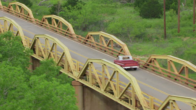 vidéos et rushes de ws aerial zi ts red chevy truck driving over pony ridge on route 66 in caddo county / oklahoma, united states - oklahoma