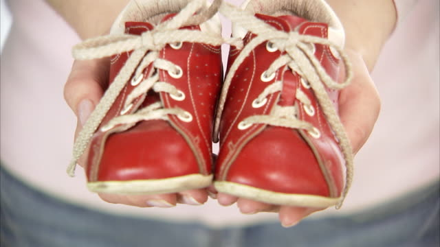 Red children's shoes in the hands of a woman close-up.